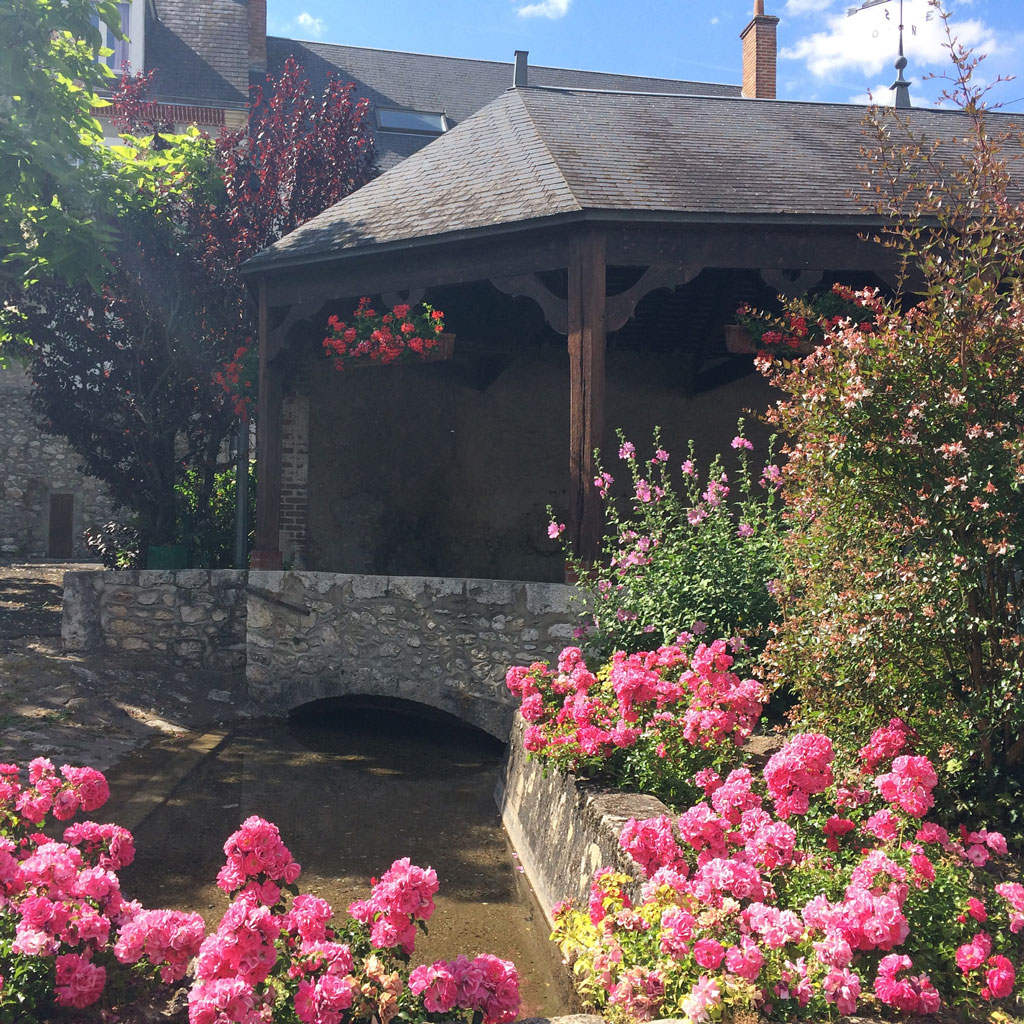 The wash house at Cour-sur-Loire surrounded by roses