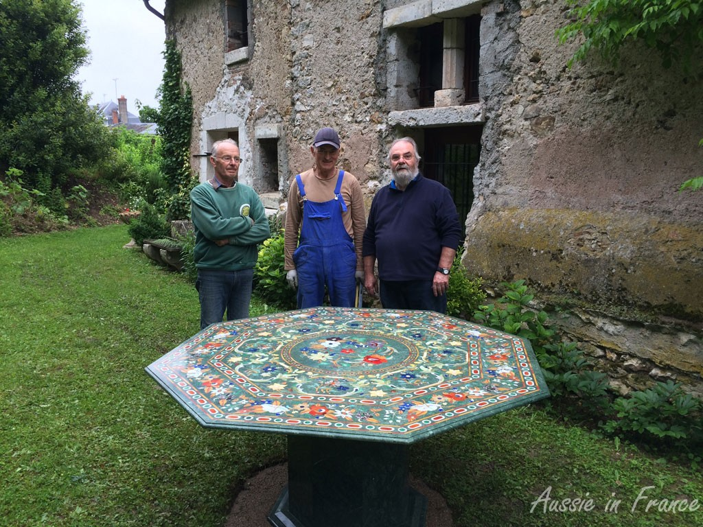 Our marble-inlay table iinstalled n its final position in the garden with the help of our neigjbour Alain and Mr Previous Owner
