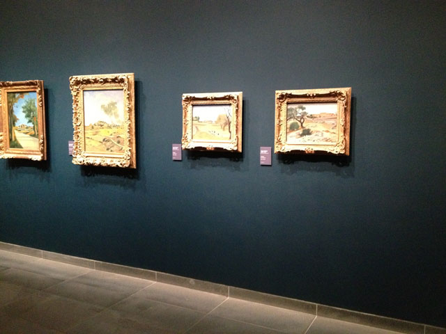 Paintings from the permanent collection on the wall inside the museum