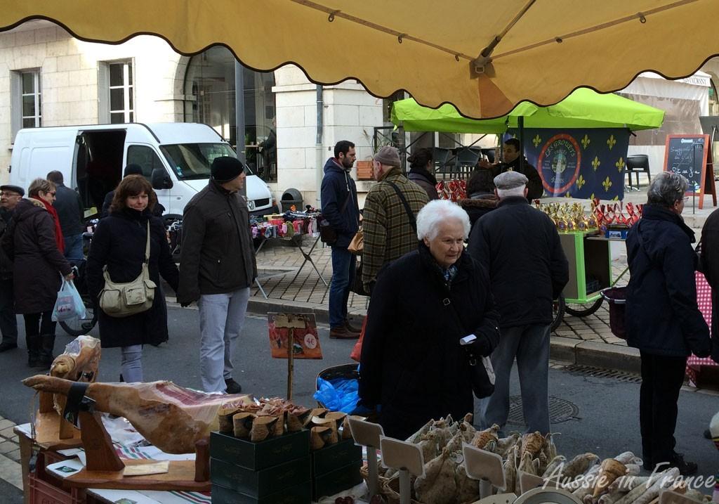 Il y avait beaucoup de monde au marché. Il y avait plusieurs personnes habillées en noir. Les gens avaient l'air content parce qu'il faisait soleil.