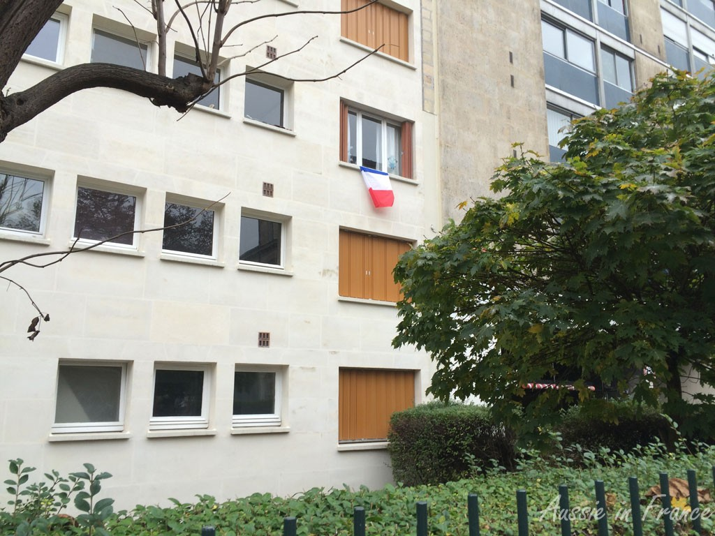 A remembrance flag on a  window in the 20th arrondissement