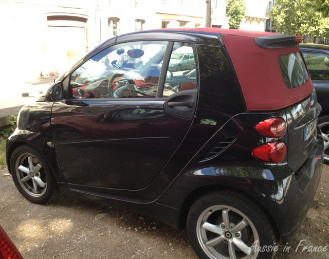 A snazzy red and black Smart car