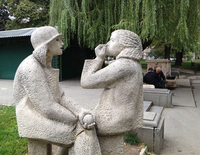 Statues in the park with chess players in the background