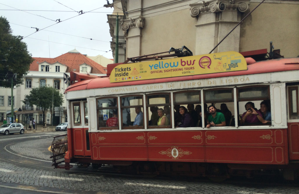 The famous n° 28 tram full of people hanging out the windows