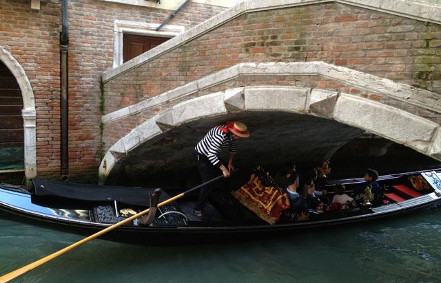 Gondolier ducking under a low bridge